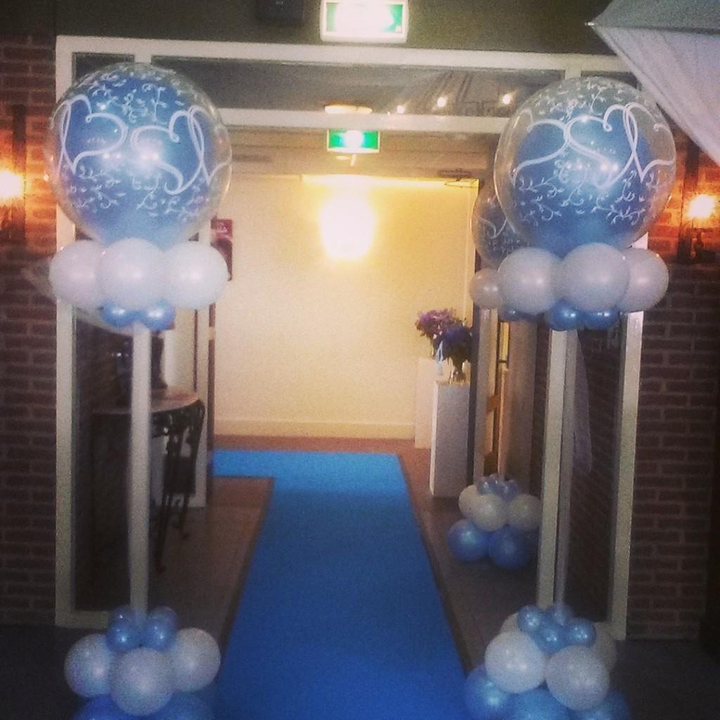 Lichtblauwe loper en helium ballonpilaren wedding bij entree feestzaal