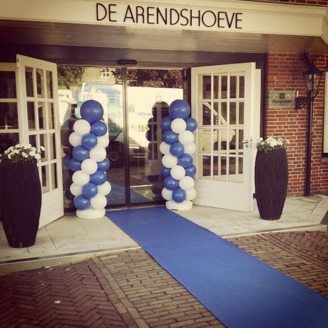Blauwe loper en ballonpilaren blauw wit bij entree feestzaal bruiloft