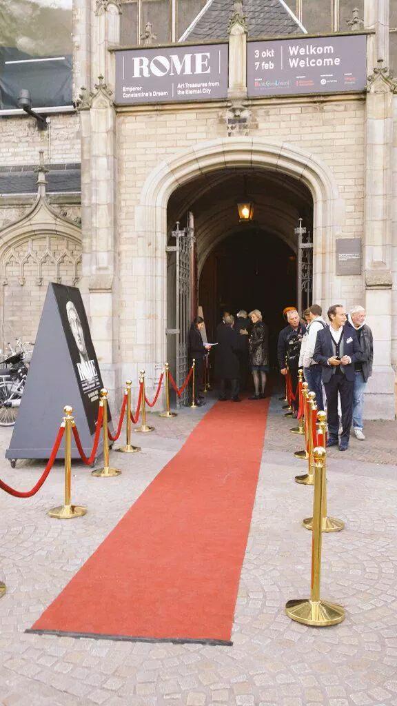 Bordeaux loper en gouden afzetpalen met rode koorden bij entree kerk