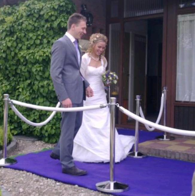 Bruidspaar op paarse loper en zilveren afzetpalen met witte koorden