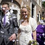 Witte rozenblaadjes strooien over bruidspaar bij stadhuis, gemeentehuis of kerk