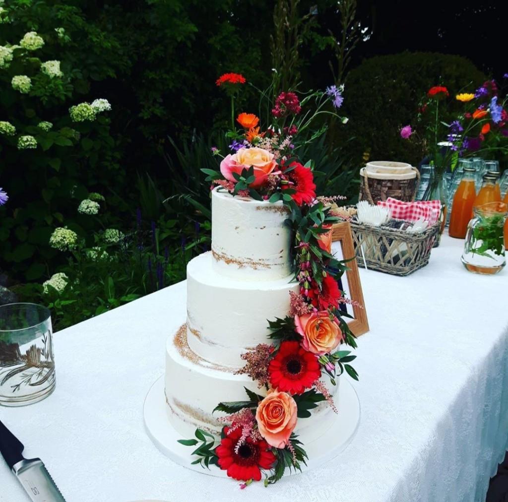Naked cake licht afgesmeerd met een waterval van echte bloemen in flower pics