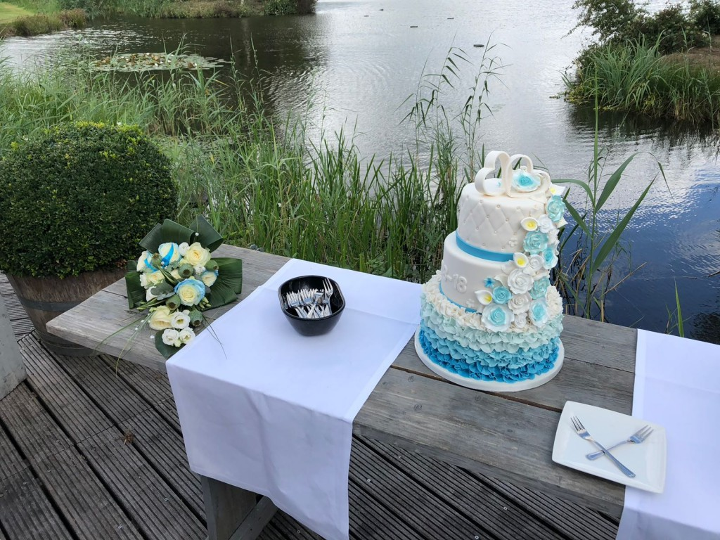 Bruidstaart in blauw tinten met roesjes, handgemaakte bloemenwaterval en chesterfield