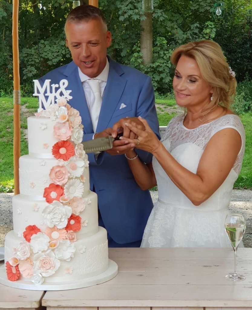 Prachtige bruidstaart met handgemaakte bloemen waterval in zalm tinten