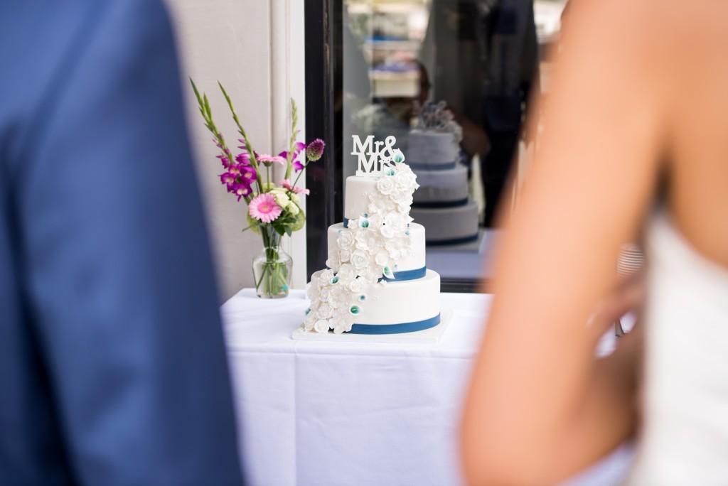 Prachtige bruidstaart met een waterval van handgemaakte bloemen in blauw/wit