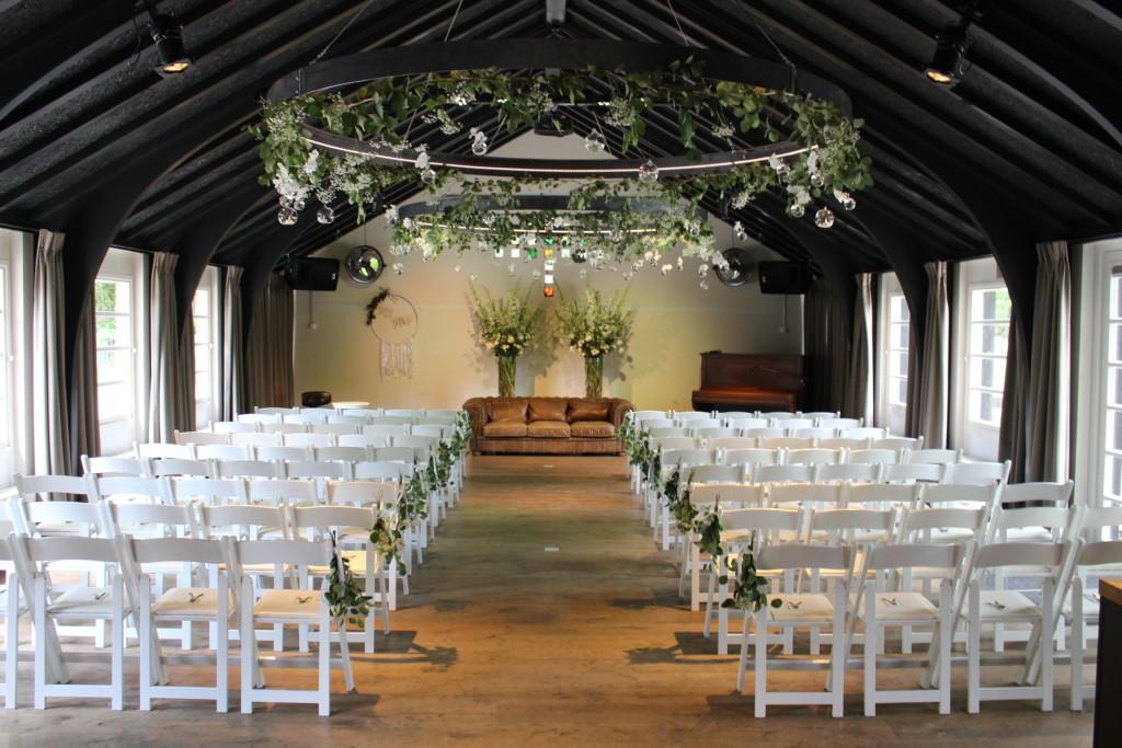 Huize Koningsbosch Zaal met witte stoelen en bloemendecoratie